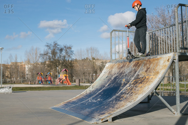 From below of active teen boy in protective helmet with kick scooter standing on ramp in skate park while preparing for performing trick in sunny spring day