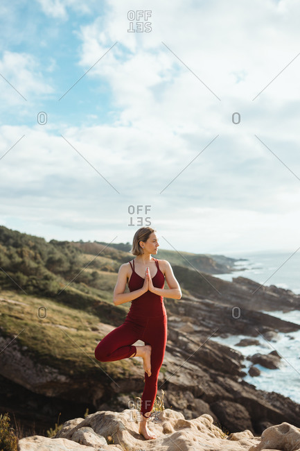 Woman looking away in red sporty wear working out and practicing tree yoga pose on empty rocky beach