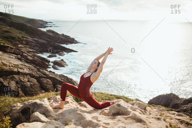 Side view of young blond haired woman with closed eyes in red sporty wear working out and practicing warrior one yoga pose on empty rocky beach
