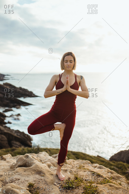 Woman with closed eyes in red sporty wear working out and practicing tree yoga pose on empty rocky beach