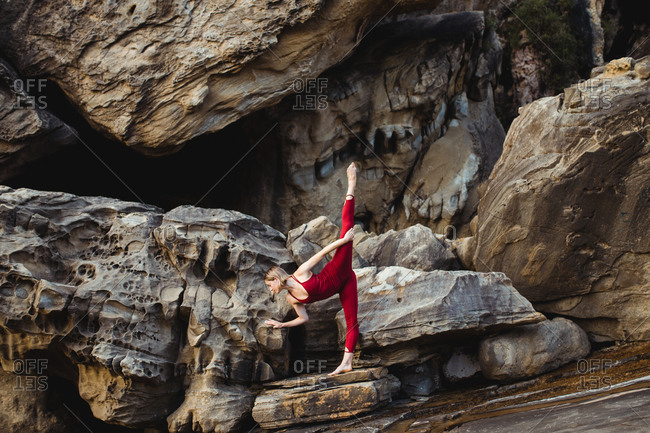 Side view of young woman in red sportswear doing downward facing dog pose standing on one leg while outstretching different leg on rough rock among mountains