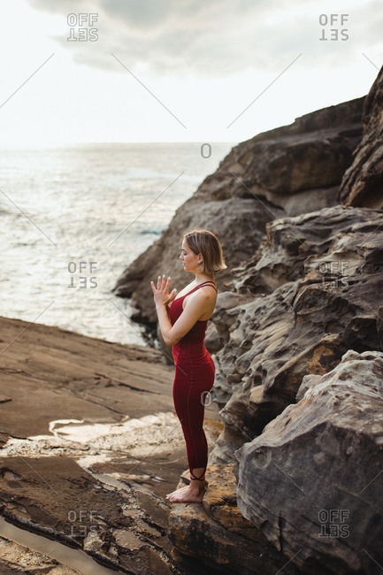 Side view of woman looking at camera in red sporty wear working out and practicing mountain pose on empty rocky beach