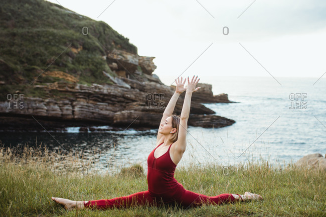 Young flexible woman in red sportswear sitting in difficult yoga monkey pose on empty green hill