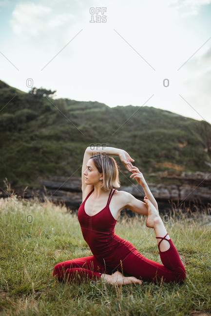 Young flexible woman in red sportswear sitting in difficult yoga one legged king pigeon pose on empty green hill