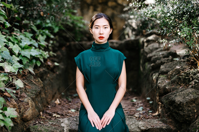 Young ethnic female in trendy dress sitting on rough stone structure near green bushes and looking at camera in aged garden
