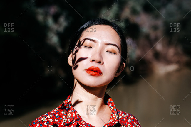 Beautiful Asian lady with closed eyes and shadow of plant twig on face standing against lake in countryside