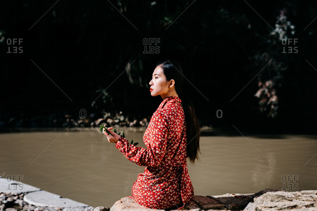 Back view of stylish ethnic female looking away while sitting in a stone fence holding thin branch near peaceful lake