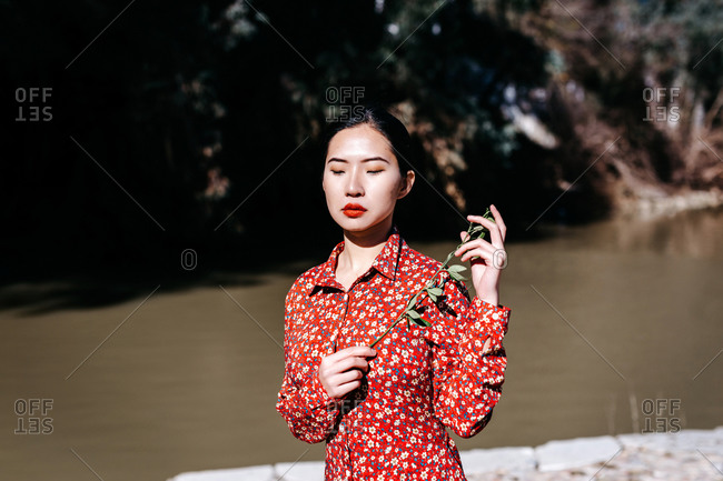 Stylish ethnic female with closed eyes holding thin branch standing near peaceful lake on cloudless day in countryside
