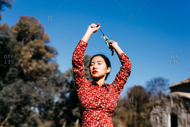 Stylish ethnic female with closed eyes holding thin branch in raised arms while standing near peaceful lake on cloudless day in countryside