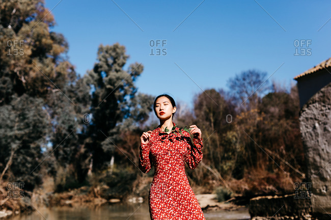 Stylish ethnic female with closed eyes holding thin branch while standing near peaceful lake on cloudless day in countryside