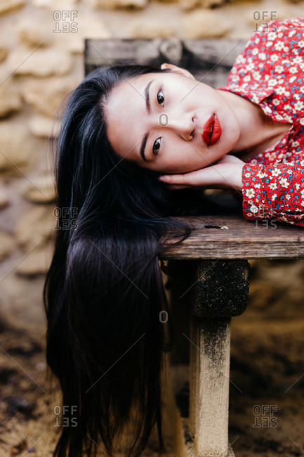 Pretty ethnic lady in trendy floral clothes lying on old lumber bench and looking at camera against stone wall