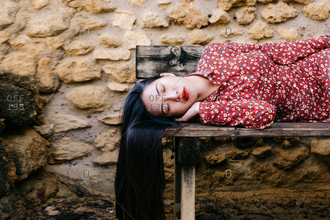 Pretty ethnic lady in trendy floral clothes lying on old lumber bench with closed eyes against stone wall