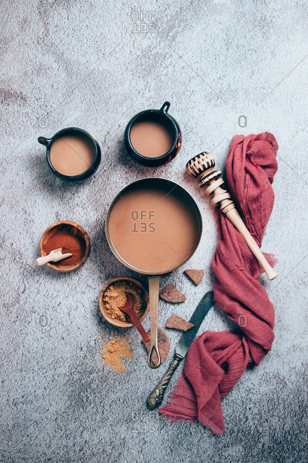 Top view of traditional Mexican spicy hot chocolate with cinnamon and red pepper powders served in pot and cups placed with chunks of chocolate and wooden whisk with red cloth on gray background
