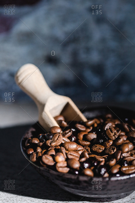 From above of black bowl with aromatic fresh roasted coffee beans and wooden serving scoop placed on table with blurred background