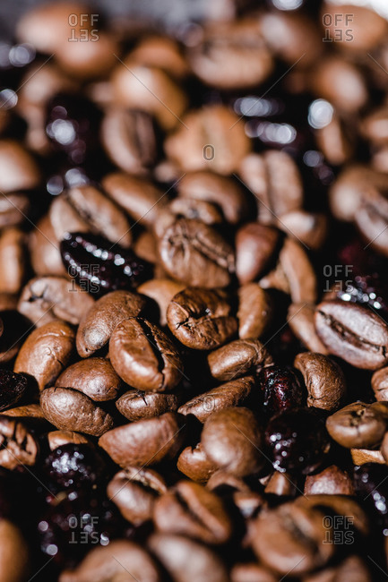 Closeup textured background with mixed black and brown fresh aromatic roasted coffee beans