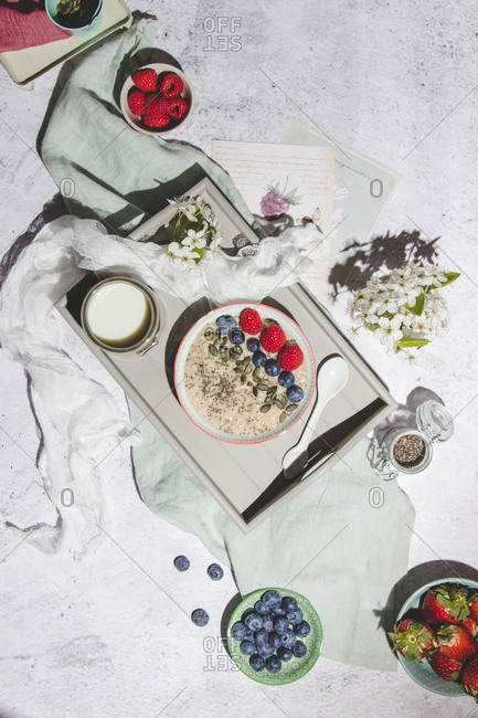 Top view of delicious healthy oat porridge with fresh berries served with cup of milk on tray placed on gray surface with berries and flowers