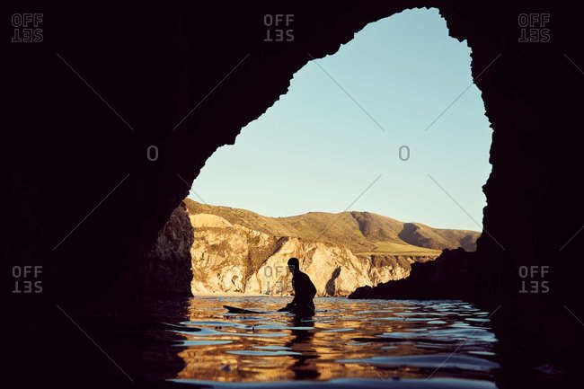 Silhouette of surfer in cave, Monterey County, California