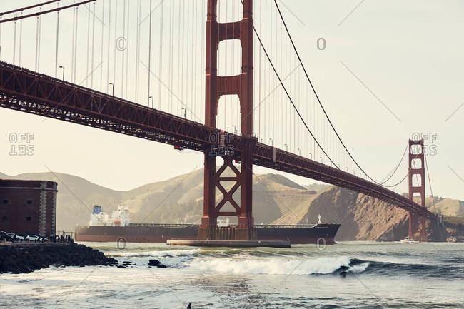 San Francisco, California - April 13, 2018: Surfers riding waves under the Golden Gate Bridge