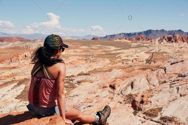 Woman sitting on cliff overlooking Valley of Fire State Park, Nevada