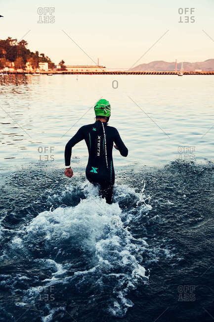 San Francisco, California - September 12, 2019: Swimmer running in the water near Ghirardelli Square