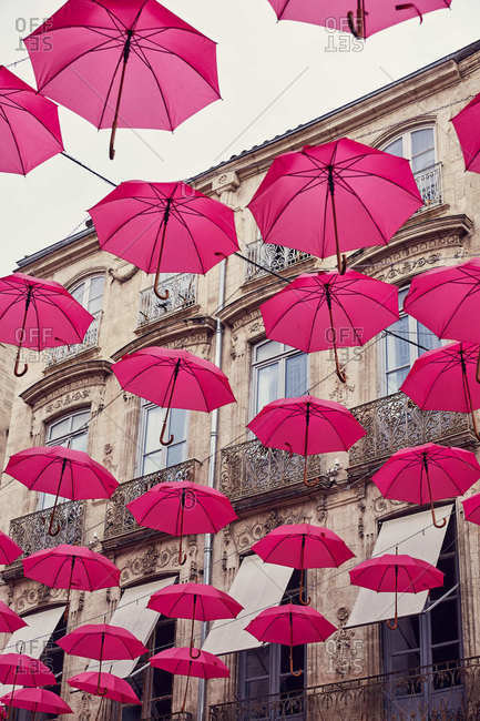Pink umbrellas hanging above the street in Montpellier, France