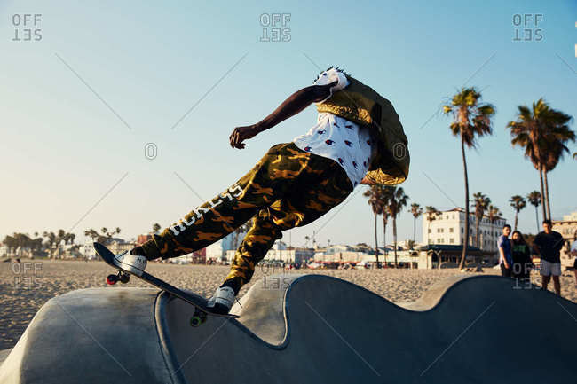 Los Angeles, California - July 7, 2019: Back view of man skateboarding at Venice Beach