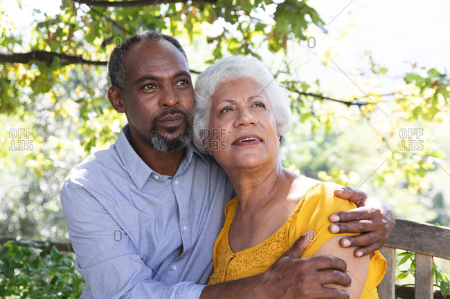 Portrait of a senior African American couple enjoying their retirement, sitting in a garden in the sun embracing and looking away smiling, couple isolating during coronavirus covid19 pandemic