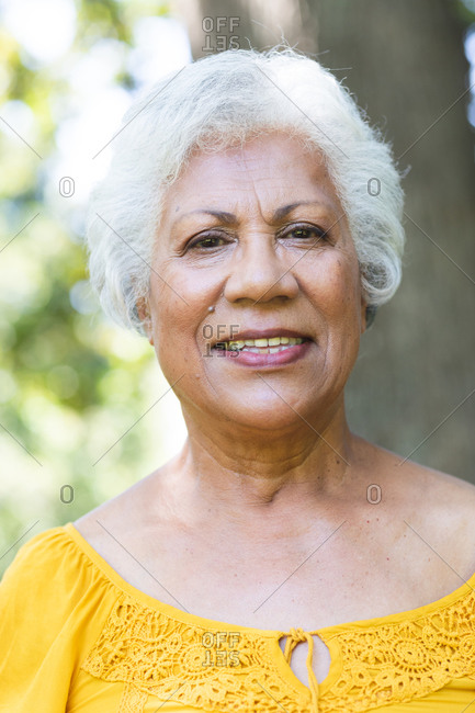 Portrait close up of an attractive senior African American woman with short white hair enjoying her retirement in a garden in the sun, looking to camera and smiling, self isolating during coronavirus covid19 pandemic