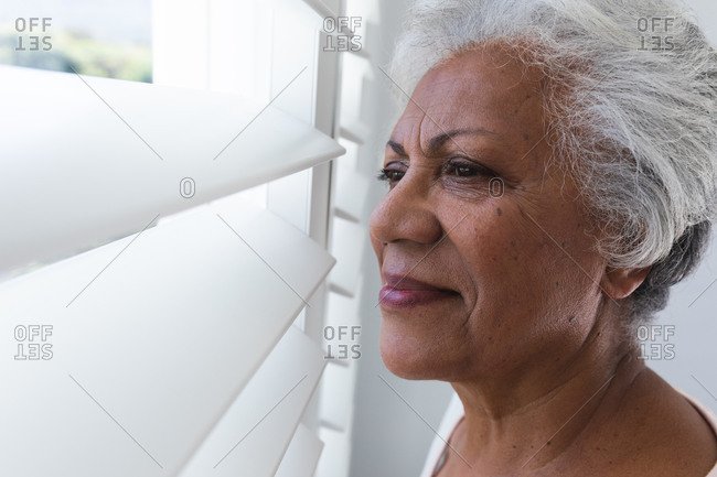 Side view close up of an attractive retired senior African American woman with short white hair at home looking out of the window between white louvred window shutters on a sunny summer day and smiling, self isolating during coronavirus covid19 pandemic