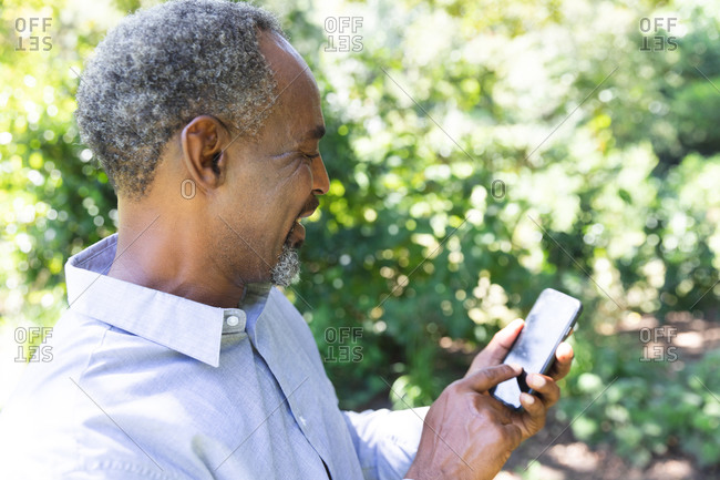 A happy handsome senior African American man enjoying his retirement, in a garden in the sun text messaging on a mobile phone and smiling