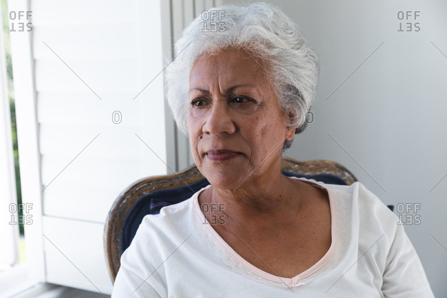 Portrait of an attractive retired senior African American woman with short white hair sitting on a chair at home by a window with white window shutters on a sunny summer day, , self isolating during coronavirus covid19 pandemic