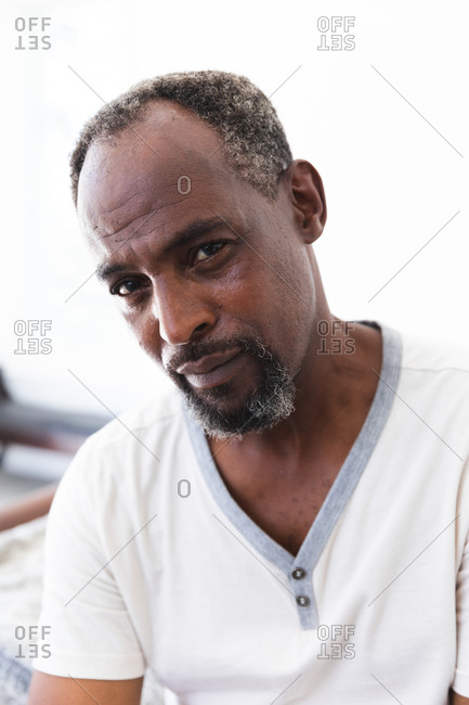 Portrait close up of a handsome senior African American man with a beard wearing a white t shirt looking to camera with a serious expression, self isolating during coronavirus covid19 pandemic