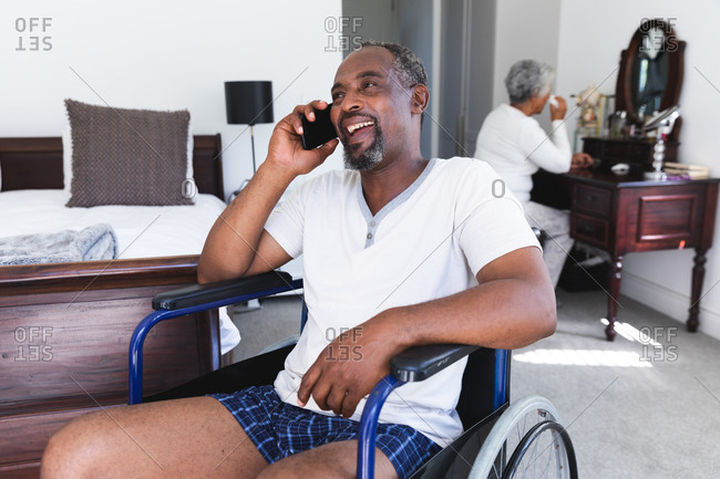 A senior retired African American couple at home in their bedroom, the man sitting in a wheelchair in his underwear talking on a smartphone and smiling, the woman sitting at her dressing table in the background, self isolating during coronavirus covid19 pandemic