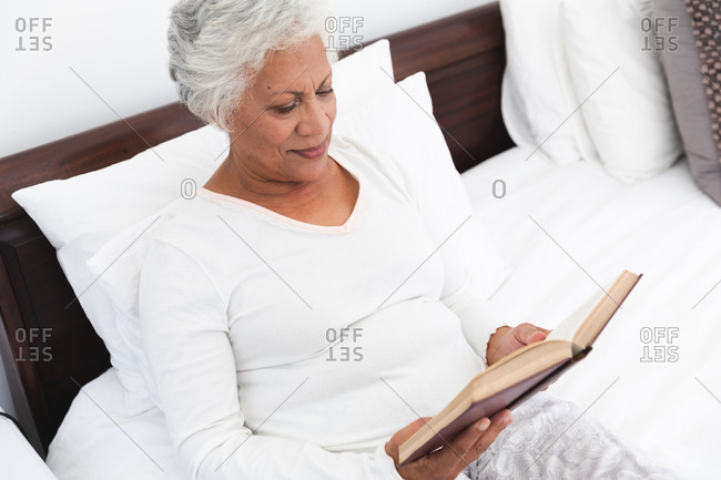 Close up of an attractive retired senior African American woman at home, sitting up in bed reading a book and smiling, self isolating during coronavirus covid19 pandemic