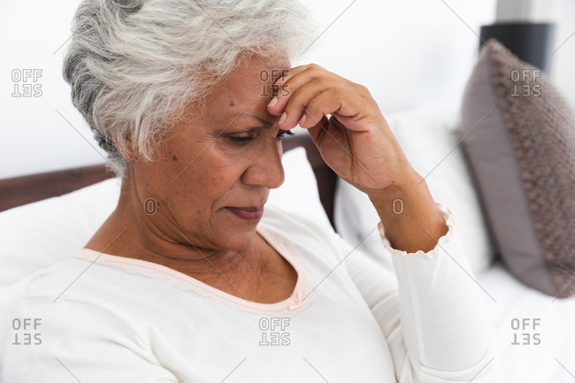 Close up of a senior retired African American woman at home sitting up in bed in her bedroom with a headache, touching her head and looking down, self isolating during coronavirus covid19 pandemic