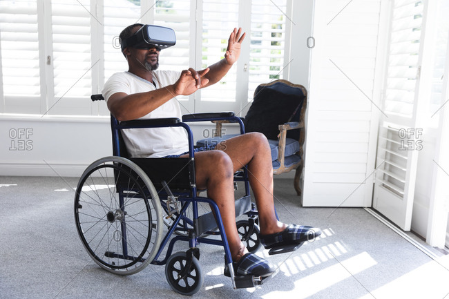 A senior retired African American man at home, sitting in a wheelchair in his underwear in front of a window on a sunny day using a VR headset with his arms outstretched in front of him, self isolating during coronavirus covid19 pandemic