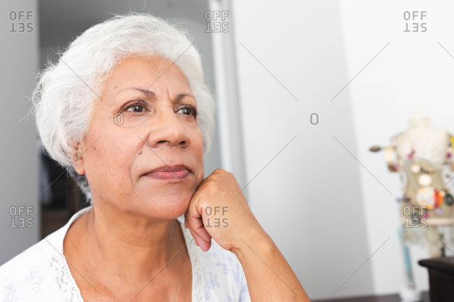 Close up of an attractive senior retired African American woman at home in her bedroom, looking away and thinking, self isolating during coronavirus covid19 pandemic