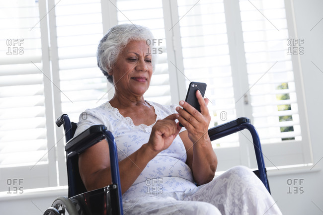A senior retired African American woman at home, sitting in a wheelchair wearing pajamas in front of a window on a sunny day using a smartphone and smiling, self isolating during coronavirus covid19 pandemic
