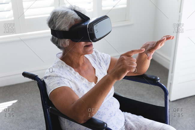 A senior retired African American woman at home, sitting in a wheelchair in her nightclothes in front of a window on a sunny day using a VR headset with her arms outstretched in front of her, self isolating during coronavirus covid19 pandemic