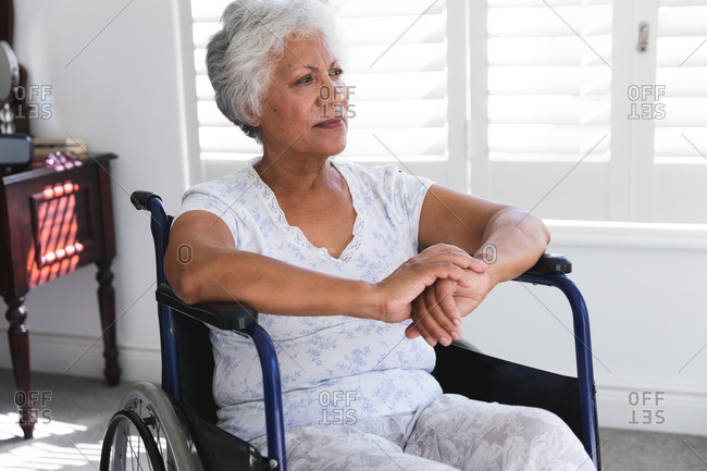 A senior retired African American woman at home, sitting in a wheelchair wearing pajamas in front of a window on a sunny day looking away in thought, self isolating during coronavirus covid19 pandemic