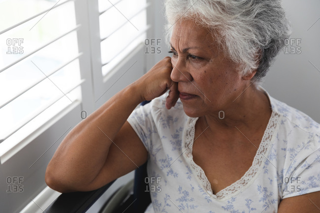 Close up of a senior retired African American woman at home, sitting in a wheelchair wearing pajamas looking out of a window on a sunny day in thought, self isolating during coronavirus covid19 pandemic