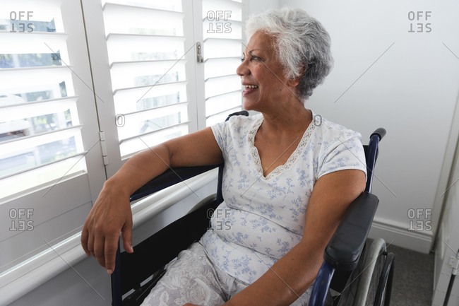 A senior retired African American woman at home, sitting in a wheelchair wearing pajamas looking out of a window on a sunny day and smiling, self isolating during coronavirus covid19 pandemic
