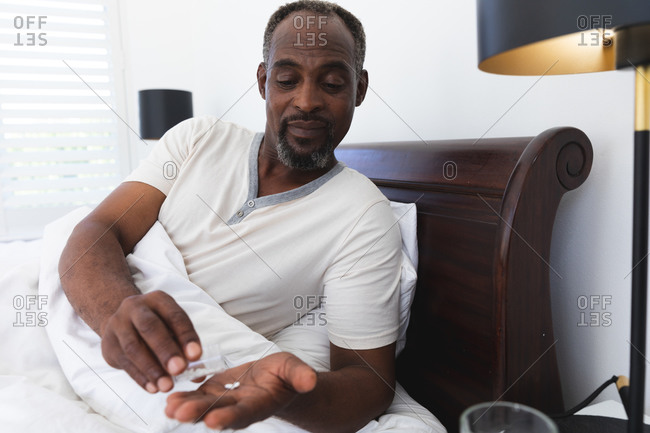 A senior retired African American man at home sitting up in bed in his bedroom, pouring tablets from a bottle into his hand and smiling before taking his medication, self isolating during coronavirus covid19 pandemic