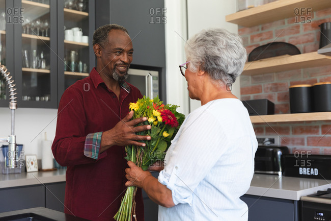 A senior African American couple enjoying their retirement, standing in their kitchen on a sunny day, the man holding a bouquet of flowers, smiling and giving them to his wife, at home together isolating during coronavirus covid19 pandemic