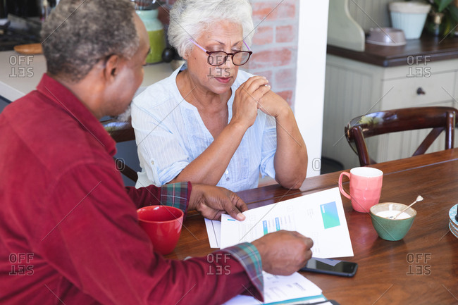 A senior retired African American couple sitting at a table in their dining room drinking coffee, looking at paperwork and discussing their finances, at home together isolating during coronavirus covid19 pandemic