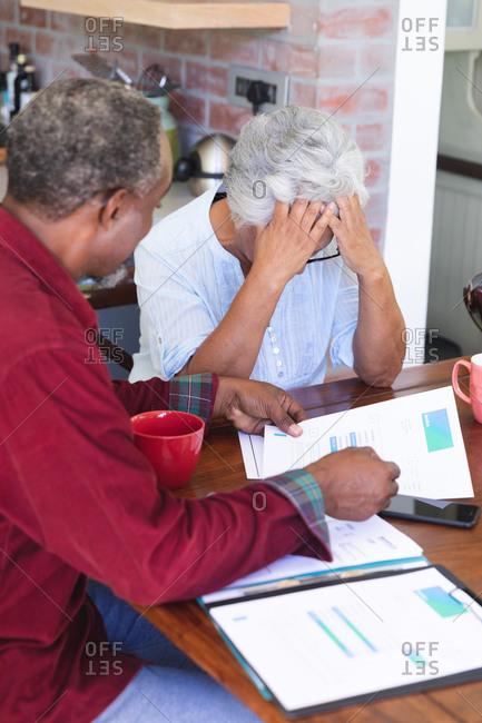 A senior retired African American couple sitting at a table in their dining room drinking coffee, looking at paperwork and discussing their finances, the woman with her head in her hands, at home together isolating during coronavirus covid19 pandemic