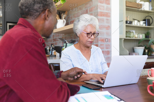 A senior retired African American couple sitting at a table in their dining room, looking at paperwork and discussing their finances, the woman using a laptop computer, at home together isolating during coronavirus covid19 pandemic