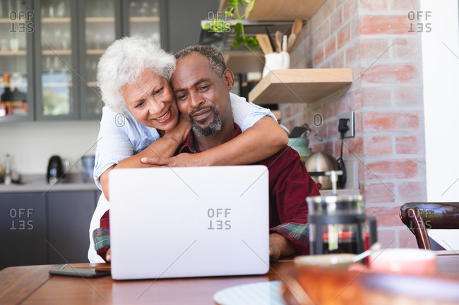 A happy senior retired African American couple at a table in their dining room, using a laptop computer together, the man sitting and the woman standing behind and embracing him, both smiling, at home together isolating during coronavirus covid19 pandemic