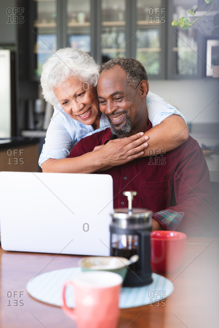 Close up of a happy senior retired African American couple at a table in their dining room, using a laptop computer together, the man sitting and the woman standing behind and embracing him, both smiling, at home together isolating during coronavirus covid19 pandemic