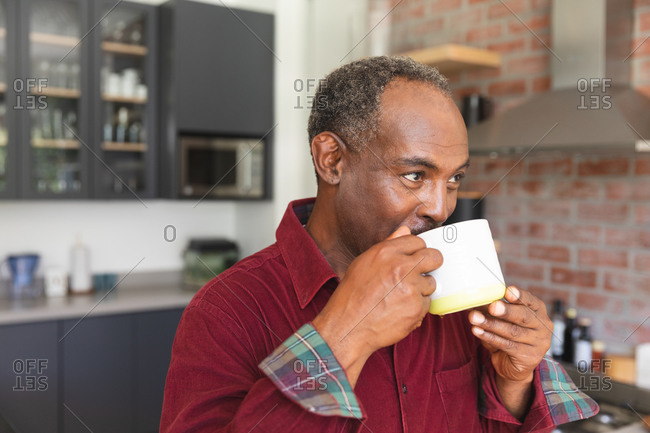 Happy senior retired African American man at home standing in the kitchen, smiling and drinking a mug of coffee, at home isolating during coronavirus covid19 pandemic